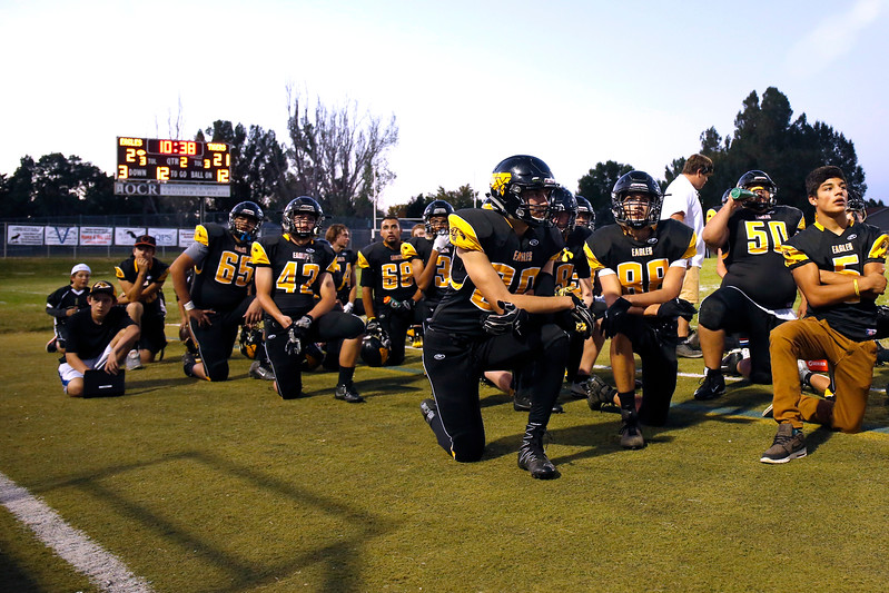 Thompson Valley Eagles take a knee as the game stops for an emergency in the stands on Thurdsay, Sept. 21, 2017 at Patterson field. (Photo by Lauren Cordova/Loveland Reporter-Herland)