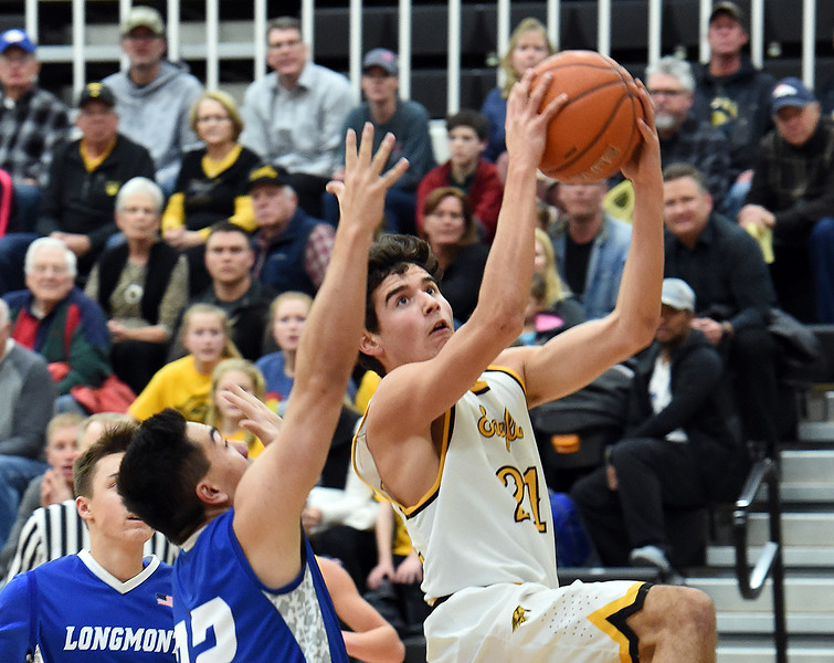 Thompson Valley's (21) Adrian Juarez goes up for a shot past Longmont's (22) Oakley Dehning during their game Tuesday, Jan. 23, 2018, at Thompson Valley High School in Loveland.  (Photo by Jenny Sparks/Loveland Reporter-Herald)