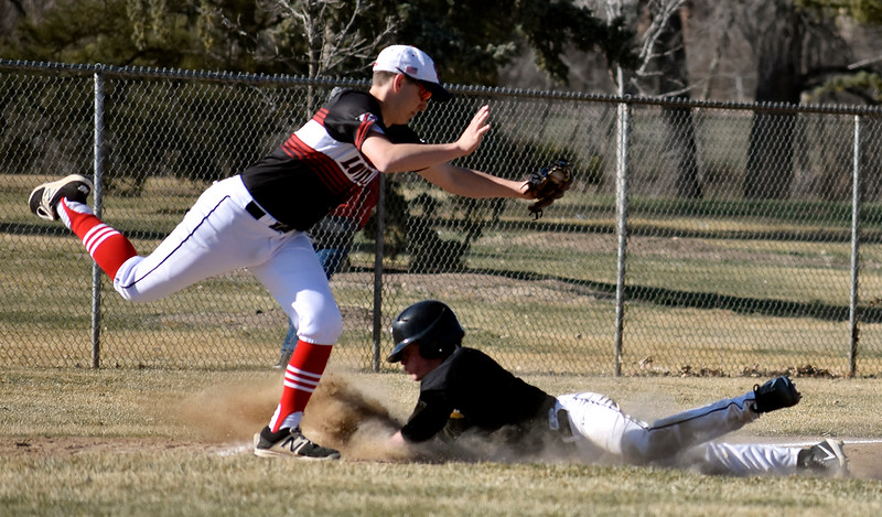 Thompson Valley's (3) Jarret Riehl slides into third base as Loveland's (6) Jackson Bakovich catches the ball to tag him out during their game on Tuesday, March 27, 2018 at Centennial Baseball Complex in Loveland. Photo by Thieng Mai/Loveland Reporter-Herald.