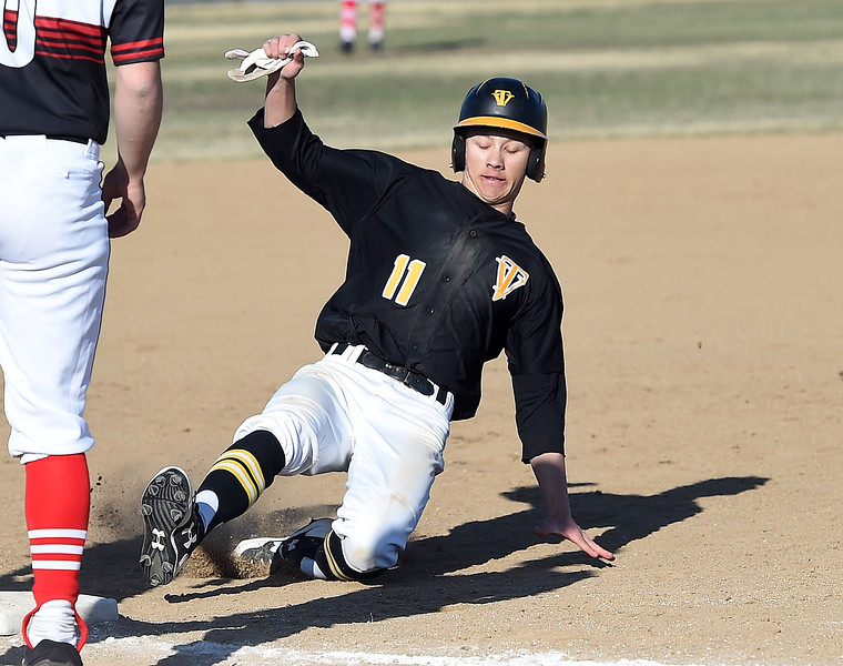 Thompson Valley's (11) Tristan Schatz slides into third base during their game against Loveland Tuesday, March 27, 2018, at Swift Field in Loveland.  (Photo by Jenny Sparks/Loveland Reporter-Herald)