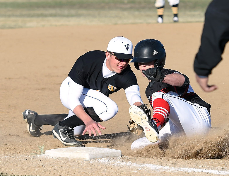 Loveland's (9) Tyler Hamill slides into third base as Thompson Valley's (4) Cameron Nellor tries to tag him during their game Tuesday, March 27, 2018, at Swift Field in Loveland.  (Photo by Jenny Sparks/Loveland Reporter-Herald)
