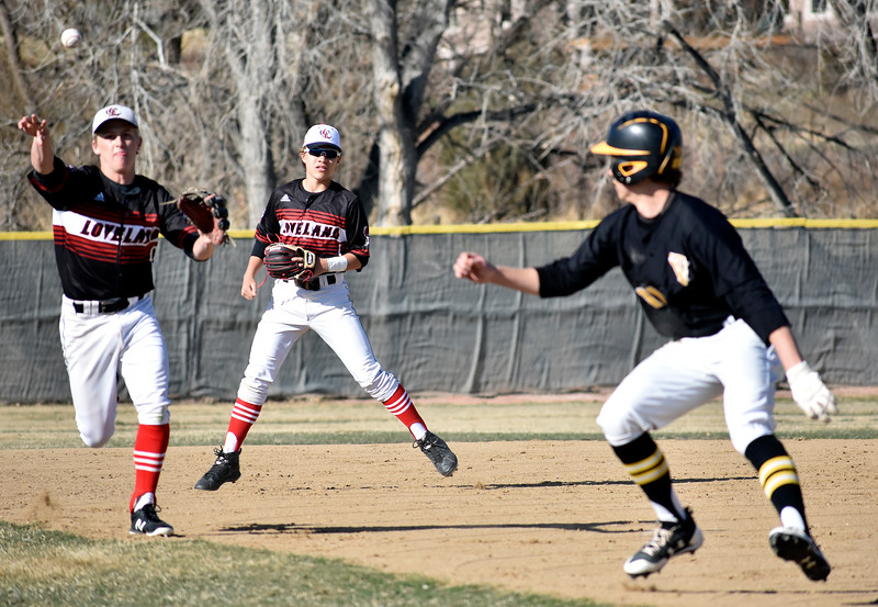 Loveland's (9, left) Tyler Hamill and (1, center) Jaxon Cabrera force Thompson Valley's (11, right) Tristan Shatz back to first base during their game on Tuesday, March 27, 2018 at Centennial Baseball Complex in Loveland. Photo by Thieng Mai/Loveland Reporter-Herald.