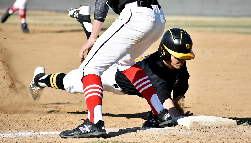 Thompson Valley's (11) Tristan Schatzl manages to slide safely back to first base before Loveland's (7) Zach Harstad can tag him out during their game on Tuesday, March 27, 2018 at Centennial Baseball Complex in Loveland. Photo by Thieng Mai/Loveland Reporter-Herald.