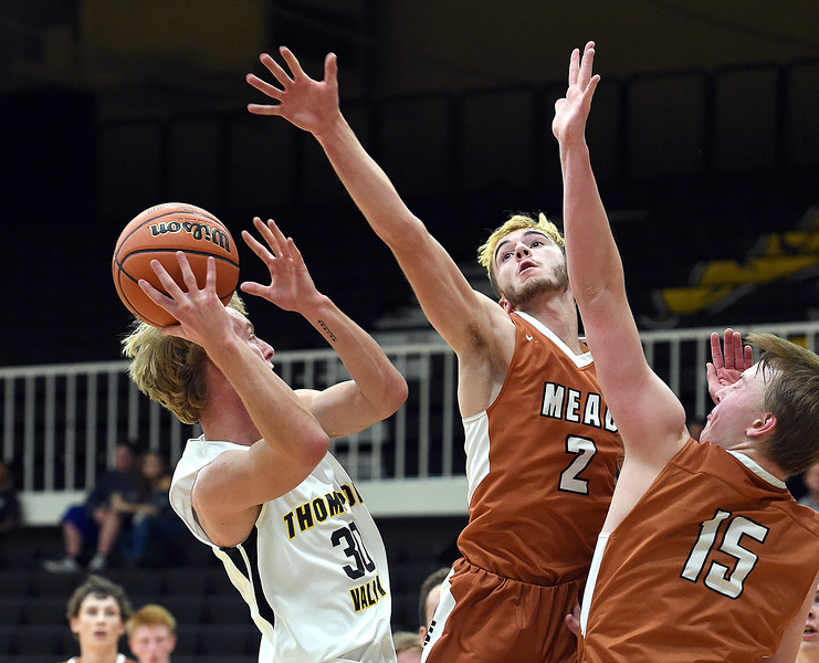 Thompson Valley's Andrew Wiersema goes up for a shot as Mead's Nick Jacobs, center, and Jax Wilke try to block during their game Tuesday, Dec. 11, 2018, at Thompson Valley in Loveland.   (Photo by Jenny Sparks/Loveland Reporter-Herald)