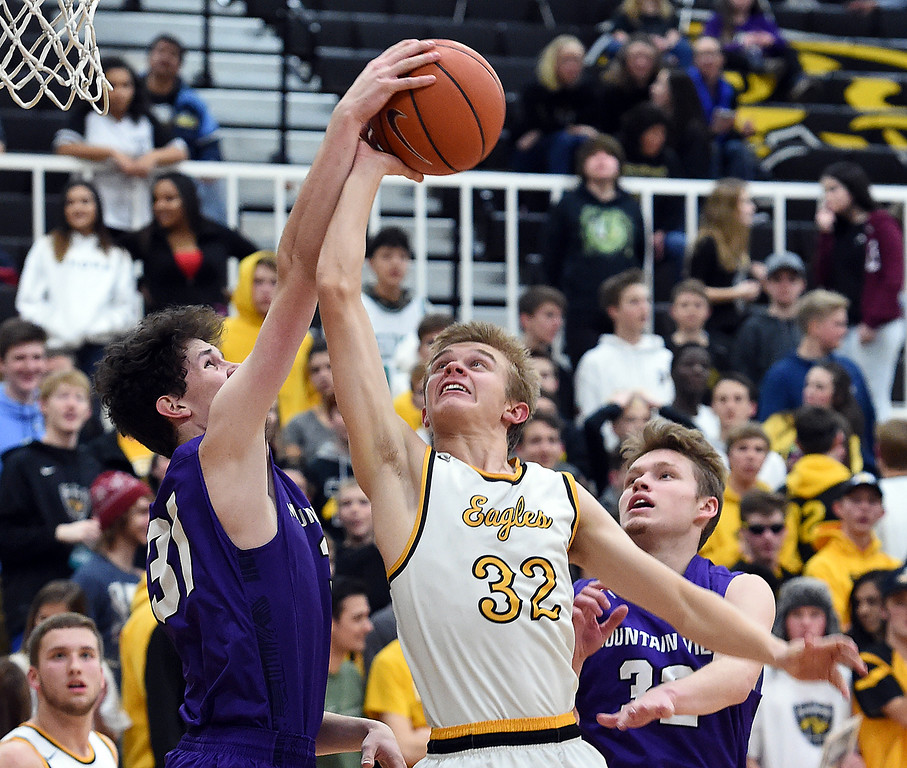Thompsn Valley's (32) Darren Edwards goes up for a shot as Mountain View's (31) Brian Flohr tries to block him during their game Wednesday, Jan. 24, 2018, at Thompson Valley in Loveland.  (Photo by Jenny Sparks/Loveland Reporter-Herald)