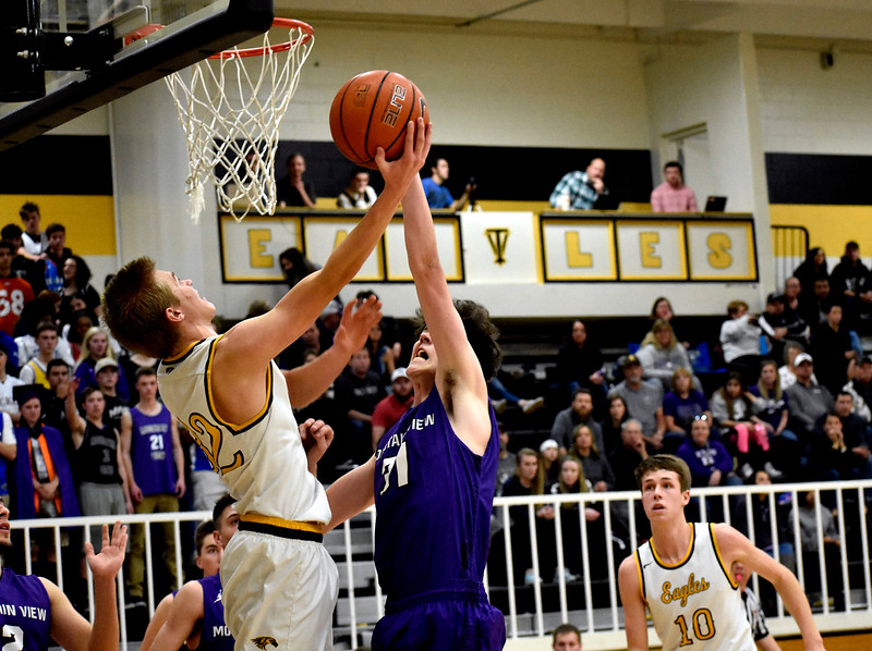 Thompson Valley's (32) Darren Edwards goes for a shot backwards as Mountain View's (31) Brian Flohr attempts to swat it away during their game on Friday, Jan. 26, 2018 at Thompson Valley High School in Loveland. Photo by Thieng Mai.