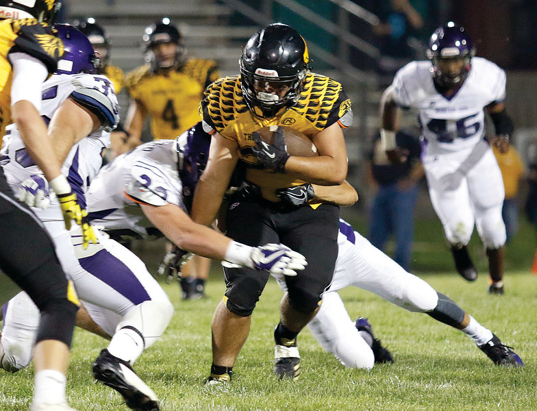 Eagles' running back, senior, Tyler Ewy-Selph (#20) pushes through an attempted tackle by two Mountain Lions' players near the 40 yard line in the secoond quarter of the game. (Lauren Cordova/ Loveland Daily Reporter Herald)