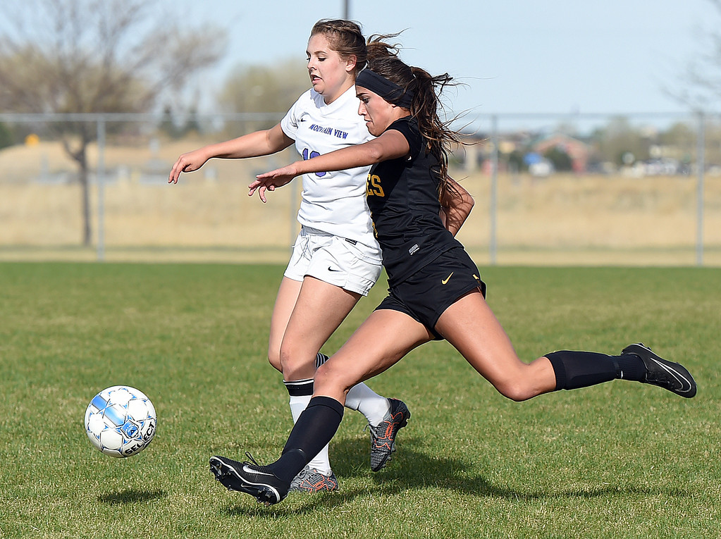 . Thompson Valley\'s #6 Kaili Campbell takes the ball down field as Mountain View\'s #13 Ashtonn Tucker tries to block Tuesday, April 18, 2017, during their game at Mountain View High School in Loveland. (Photo by Jenny Sparks/Loveland Reporter-Herald)
