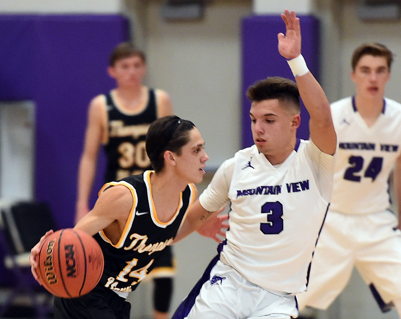 Thompson Valley's #14 Julian Espinoza takes the ball down court as Mountain View's #3 Jeremiah Greylock stays close during their game Friday, Jan. 6, 2017, at Mountain View High School in Loveland. (Photo by Jenny Sparks/Loveland Reporter-Herald)