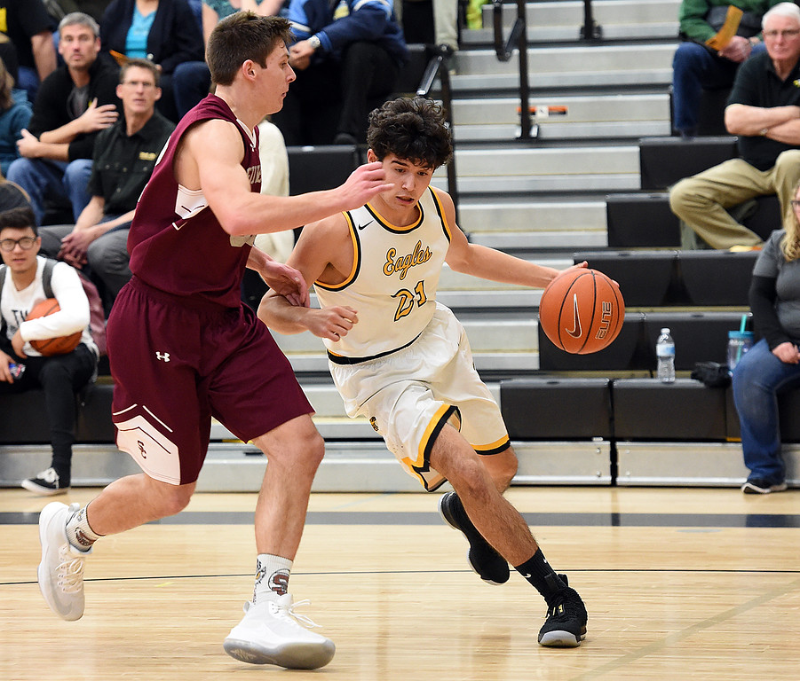 Thompson Valley's (21) Adrian Juarez dribbels past Silver Creek's (32) Trevor Riters during their game Tuesday, Feb. 6, 2018, at Thompson Valley in Loveland. (Photo by Jenny Sparks/Loveland Reporter-Herald)
