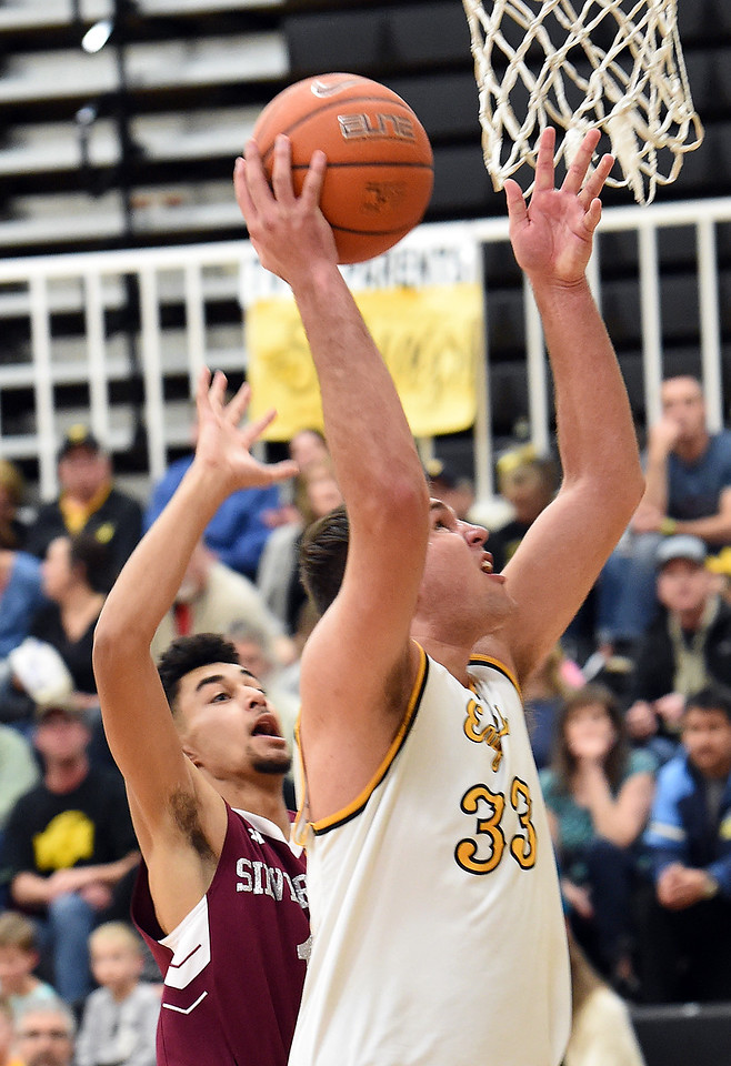 Thompson Valley's (33) Jared Kasprzak goes up for a shot past Silver Creek's (11) Joe Roth-Bogrett during their game Tuesday, Feb. 6, 2018, at Thompson Valley in Loveland. (Photo by Jenny Sparks/Loveland Reporter-Herald)