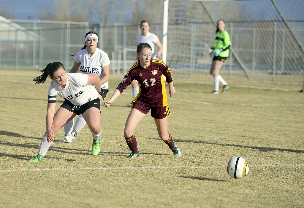 . Thompson Valley\'s Anna Mihaly and Windsor\'s Abby Gearhart got for the ball during the first half of Friday\'s match at the MVHS field. Gearhart scored three goals in the Wizards\' 6-1 win. (Mike Brohard/Reporter-Herald)