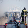 A firefighter looks on at smoke pouring from a house fire at 55-59 Parker St. in Lowell on Friday. Lowell Sun/Chris Lisinski