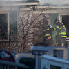 Firefighters attempt to breach a wall at 55-59 Parker St. in Lowell while battling a fire Friday morning. Lowell Sun/Chris Lisinski