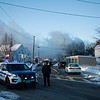 Smoke from the house fire at 55-59 Parker St. in Lowell rises over the neighborhood. Lowell Sun/Chris Lisinski