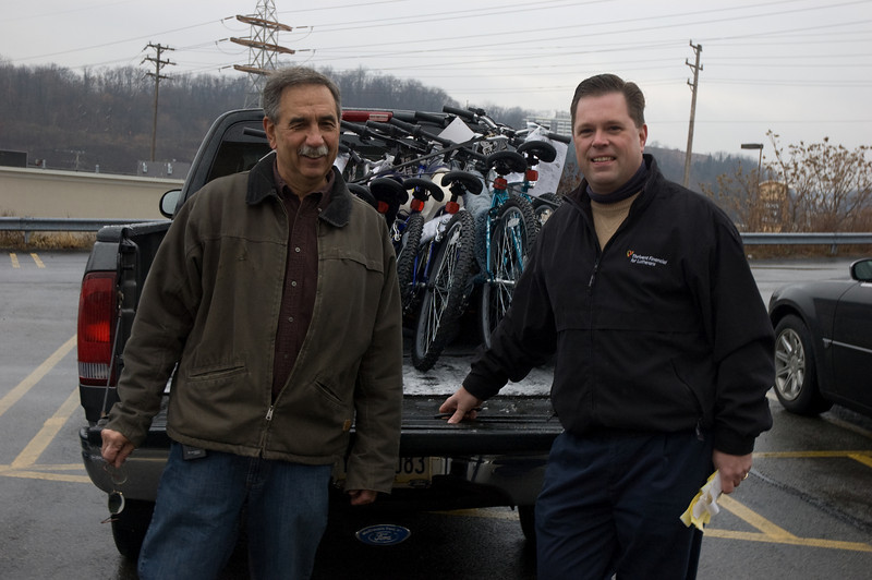 Thrivent member & volunteer Al Duss with Financial Consultant Al Todd load a group of bikes.