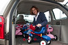Amy Todd packs tricycles into a van.