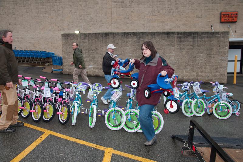 Peg VanDyke loads tricycles.