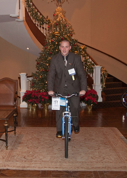 Shane Yoest demonstrates the quickest way to move the bikes to the truck. This was the first time a bicycle was ridden in the lobby of the Club at Nevillewood.