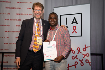22nd International AIDS Conference (AIDS 2018) Amsterdam, Netherlands.   Copyright: Steve Forrest/Workers' Photos/ IAS  Photo shows: President-Elect of the IAS, Anton Pozniak, with Mark Wainberg Fellowship Programme Award winner Victor Hamilton Singano, during the IAS Members' Meeting.