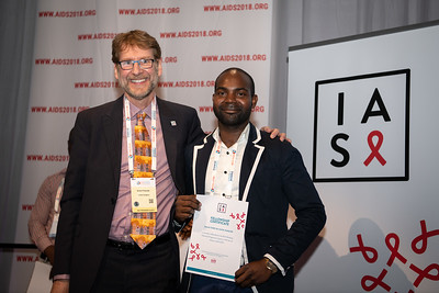 22nd International AIDS Conference (AIDS 2018) Amsterdam, Netherlands.   Copyright: Steve Forrest/Workers' Photos/ IAS  Photo shows: President-Elect of the IAS, Anton Pozniak, with Mark Wainberg Fellowship Programme Award winner Leonid Tome Da Costa Joaquim during the IAS Members' Meeting.