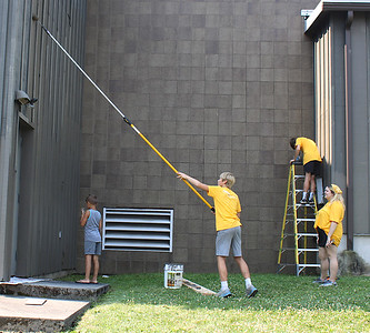 JOHN E. USALIS/STAFF PHOTOCarter Bruckhart, 15, of Manheim, uses an extension pole for a roller to paint the Ashland Municipal Building on Wednesday as part of the Crossfire Youth Ministries sprucing up project in the borough.