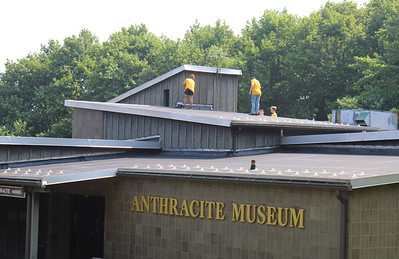 JOHN E. USALIS/STAFF PHOTOMembers of Crossfire Youth Ministries spent much of Wednesday painting the wood surfaces of the Ashland Municipal Building/Anthracite Museum at Higher Up Park as part of the ministries summer project this week. The youth here were raised to the flat portions of the roof using a bucket lift wearing safety harnesses.