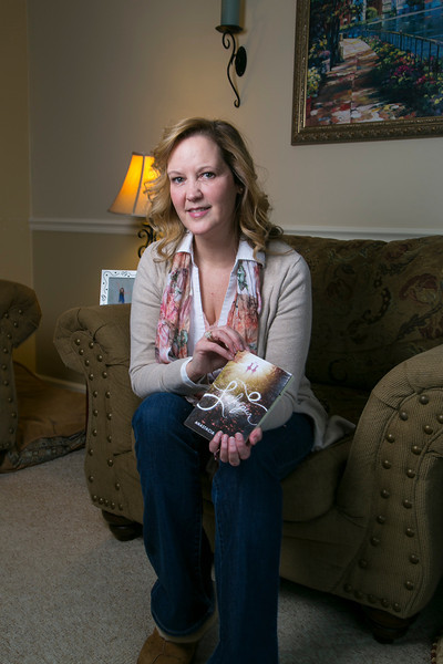 Maple Grove, MN - MPG Feb 2014 Author Hawkins: Anastacia Hawkins, author of a fictional book she wrote that was inspired by her daughter's dance class (photo of her daughter is in a frame at left) at her home here today, Monday December 30. 2013  Photo by © Todd Buchanan 2013 Technical Questions: todd@toddbuchanan.com