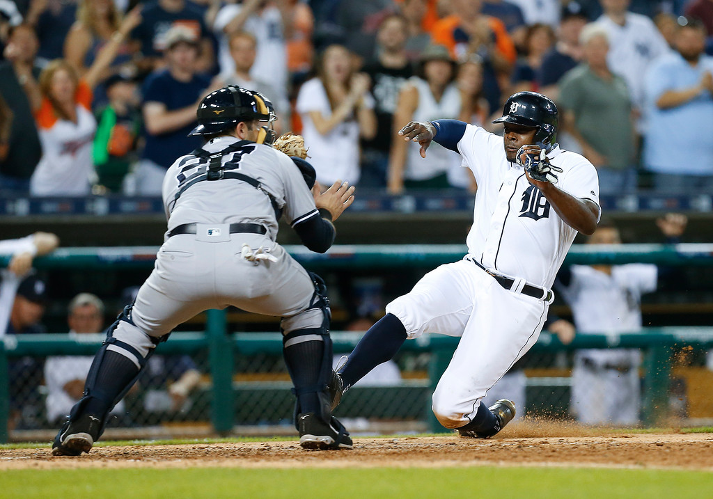 . Detroit Tigers\' Justin Upton slides into home plate as New York Yankees catcher Austin Romine (27) waits for the throw on a Ian Kinsler double in the eighth inning of a baseball game in Detroit, Thursday, June 2, 2016. Upton was tagged out on the play. (AP Photo/Paul Sancya)