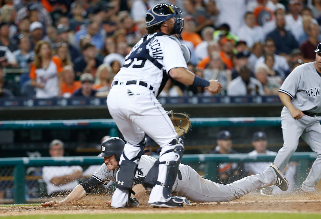 . New York Yankees\' Chase Headley dives safely into home plate as Detroit Tigers catcher Jarrod Saltalamacchia waits for the throw on a Robert Refsnyder single during the seventh inning of a baseball game in Detroit, Thursday, June 2, 2016. (AP Photo/Paul Sancya)