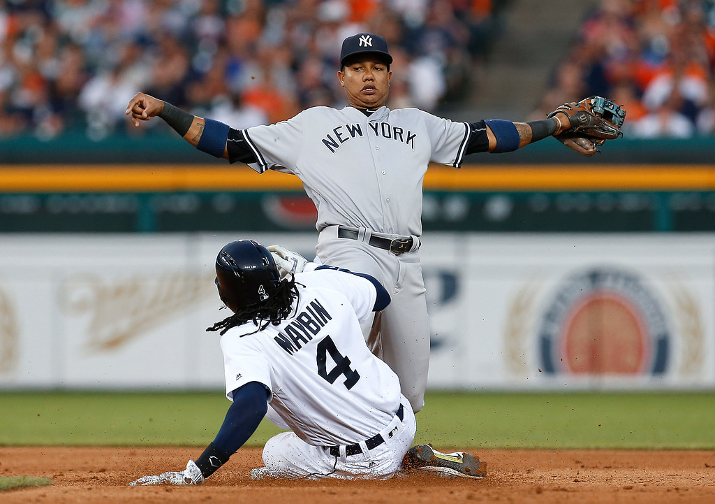 . New York Yankees second baseman Starlin Castro reaches to tag second base for an out as Detroit Tigers\' Cameron Maybin (4) slides on a J.D. Martinez ground ball during the fifth inning of a baseball game in Detroit, Thursday, June 2, 2016. (AP Photo/Paul Sancya)