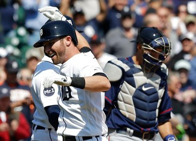 . Detroit Tigers\' Andrew Romine is greeted at home plate after his grand slam during the fourth inning of a baseball game against the Minnesota Twins, Wednesday, April 12, 2017, in Detroit. (AP Photo/Carlos Osorio)