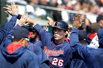 . Minnesota Twins\' Max Kepler is greeted in the dugout after he and Eddie Rosario scored on a Joe Mauer single during the third inning of a baseball game against the Detroit Tigers, Wednesday, April 12, 2017, in Detroit. (AP Photo/Carlos Osorio)