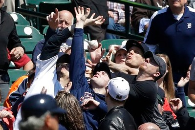 . Baseball fans reach for a foul ball hit by Minnesota Twins\' Jorge Polanco during the third inning of a baseball game against the Detroit Tigers, Wednesday, April 12, 2017, in Detroit. (AP Photo/Carlos Osorio)