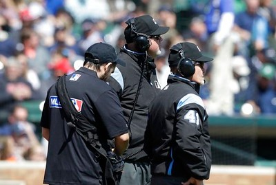 . Umpires Ron Kulpa, center, and Jerry Meals (41) review a play during the third inning of a baseball game between the Detroit Tigers and the Minnesota Twins, Wednesday, April 12, 2017, in Detroit. (AP Photo/Carlos Osorio)
