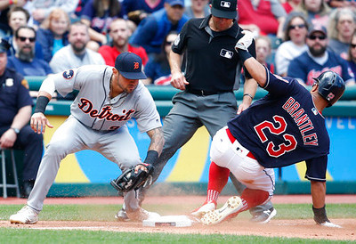 . Cleveland Indians\' Michael Brantley (23) steals third base as Detroit Tigers\' Nick Castellanos (9) attempts the tag and umpire Chris Guccione waits to make the call during the sixth inning in a baseball game, Sunday, April 16, 2017, in Cleveland. (AP Photo/Ron Schwane)