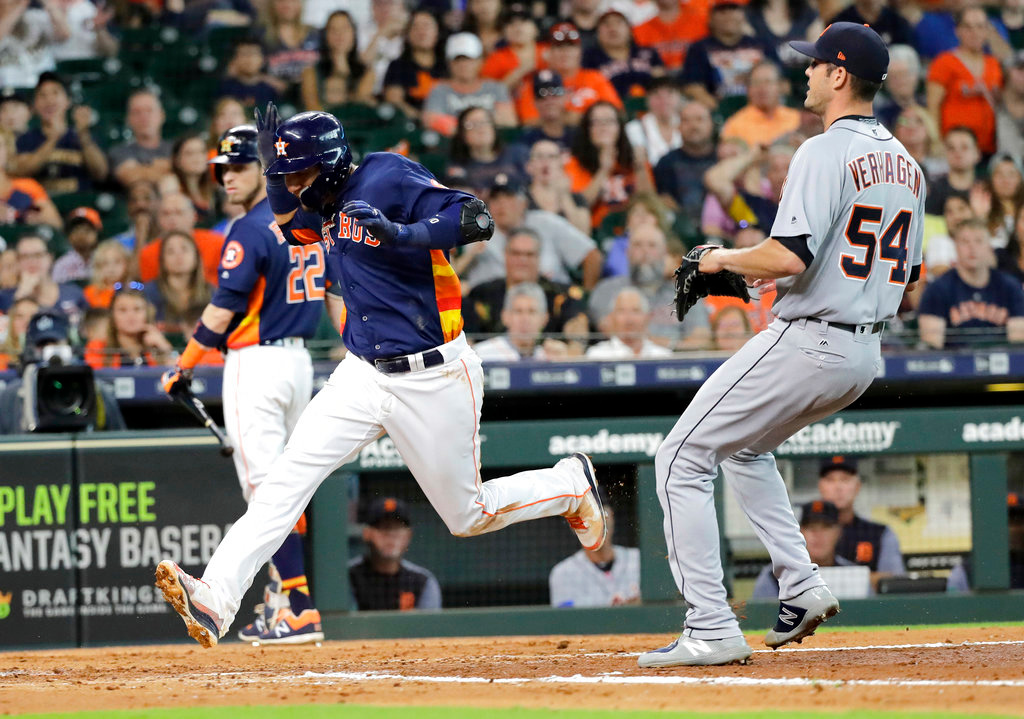 . Houston Astros\' Yuli Gurriel, left, scores after a wild pitch by Detroit Tigers pitcher Drew VerHagen (54) during the fourth inning of a baseball game Sunday, July 15, 2018, in Houston. (AP Photo/David J. Phillip)