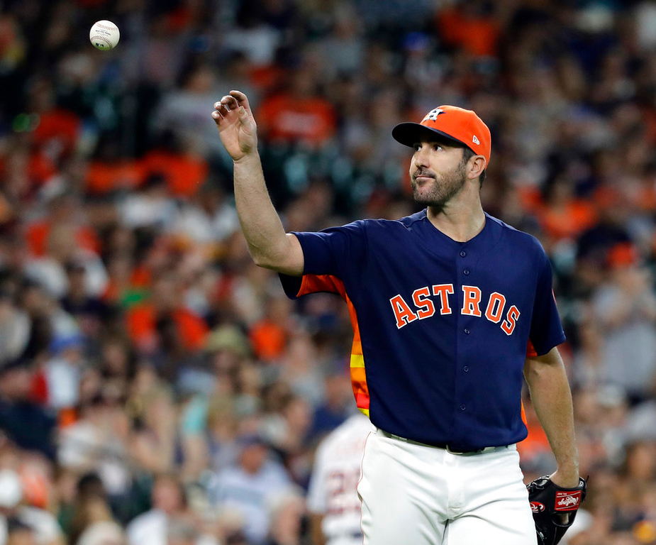 . Houston Astros starting pitcher Justin Verlander reaches for a new baseball after giving up a home run to Detroit Tigers\' Niko Goodrum during the sixth inning of a baseball game Sunday, July 15, 2018, in Houston. (AP Photo/David J. Phillip)