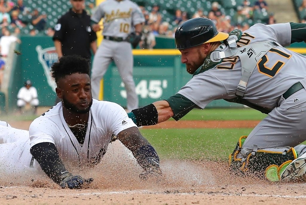. Detroit Tigers shortstop Niko Goodrum safely beats the tag of Oakland Athletics catcher Jonathan Lucroy to score from second on James McCann\'s single during the first inning of a baseball game, Tuesday, June 26, 2018, in Detroit. (AP Photo/Carlos Osorio)