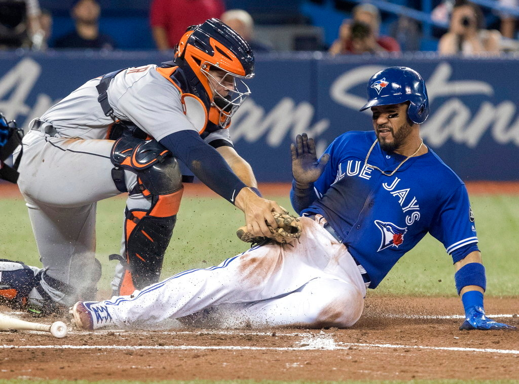 . Detroit Tigers catcher Grayson Greiner tags out Toronto Blue Jays Devon Travis at home plate in the eighth inning of a baseball game in Toronto on Saturday, June 30, 2018. (Fred Thornhill/The Canadian Press via AP)