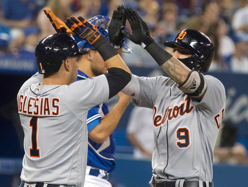 . Detroit Tigers Nicholas Castellanos, right, is greeted at home home plate by Jose Iglesias after hitting a two-run home run, scoring Iglesias, during the third inning of a baseball game against the Toronto Blue Jays in Toronto on Saturday, June 30, 2018. (Fred Thornhill/The Canadian Press via AP)