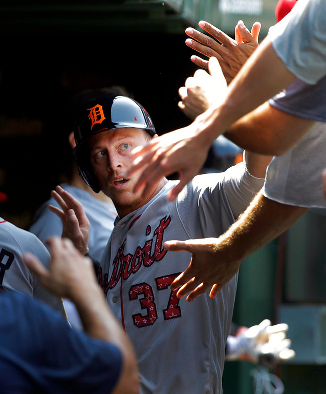 . Detroit Tigers\' Jim Adduci celebrates in the dugout after scoring on a single by James McCann during the fourth inning of a baseball game against the Chicago Cubs Tuesday, July 3, 2018, in Chicago. (AP Photo/Charles Rex Arbogast)