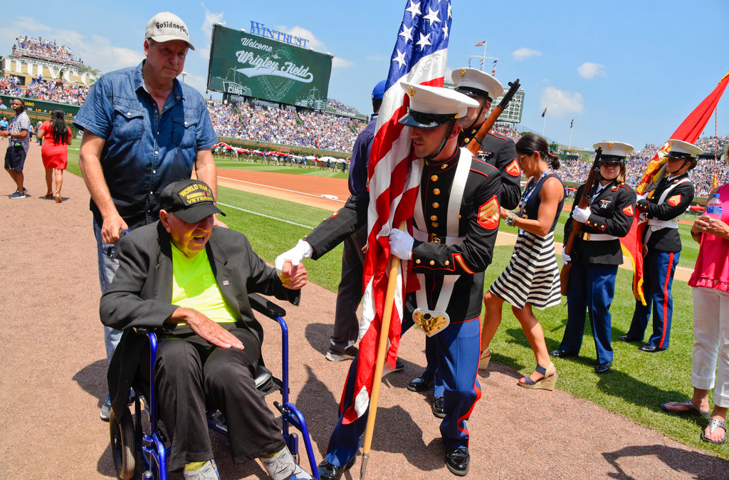 . World War II veteran Sidney Walton, left, is greeted by a member of the color guard before a baseball game between the Chicago Cubs and Detroit Tigers, Wednesday, July 4, 2018, in Chicago. (AP Photo/Matt Marton)