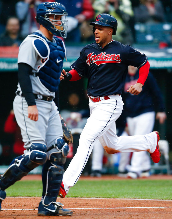 . Cleveland Indians\' Michael Brantley, right, scores past Detroit Tigers\' James McCann on a single by Yonder Alonso during the fourth inning in a baseball game, Wednesday, April 11, 2018, in Cleveland. (AP Photo/Ron Schwane)