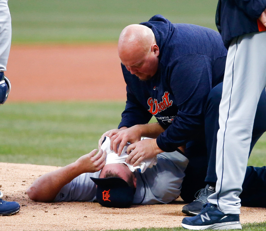 . Detroit Tigers starting pitcher Jordan Zimmermann is tended to by head athletic trainer Doug Teter after getting hit by a ball off the bat of Cleveland Indians\' Jason Kipnis during the first inning in a baseball game Wednesday, April 11, 2018, in Cleveland. (AP Photo/Ron Schwane)
