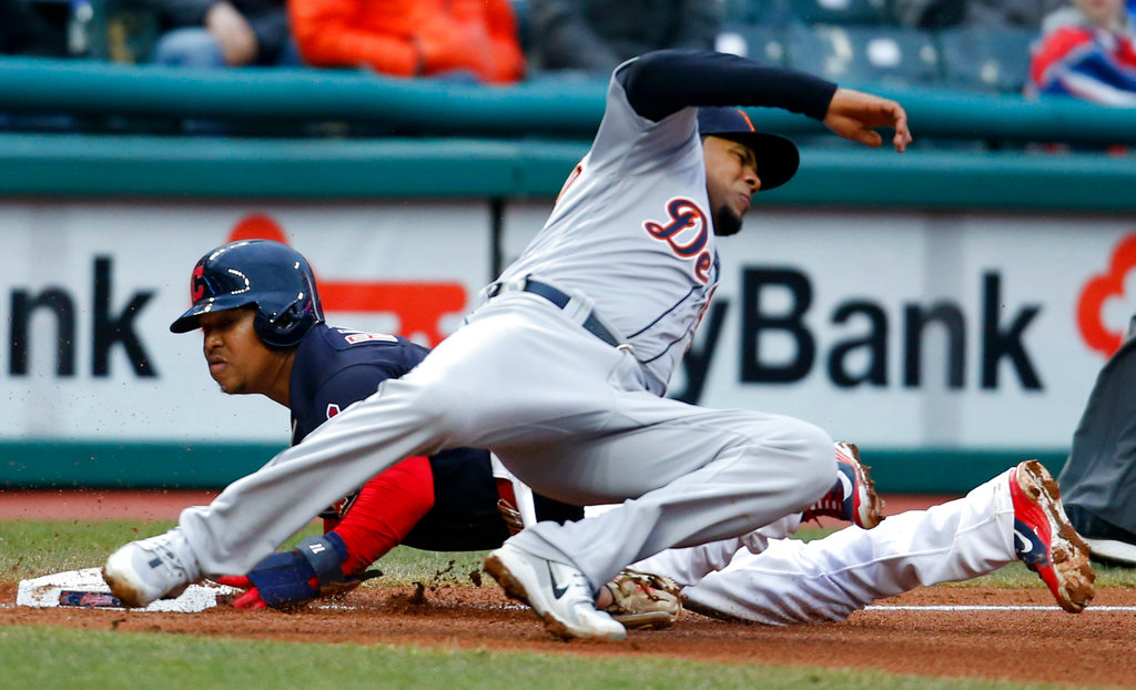 . Cleveland Indians\' Jose Ramirez steals third base as Detroit Tigers\' Jeimer Candelario attempts a tag during the fourth inning of a baseball game Wednesday, April 11, 2018, in Cleveland. (AP Photo/Ron Schwane)