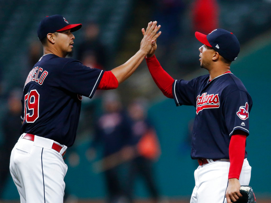 . Cleveland Indians starting pitcher Carlos Carrasco (59) celebrates with Michael Brantley after pitching a three-hitter against the Detroit Tigers in a baseball game Wednesday, April 11, 2018, in Cleveland. The Indians won 5-1. (AP Photo/Ron Schwane)