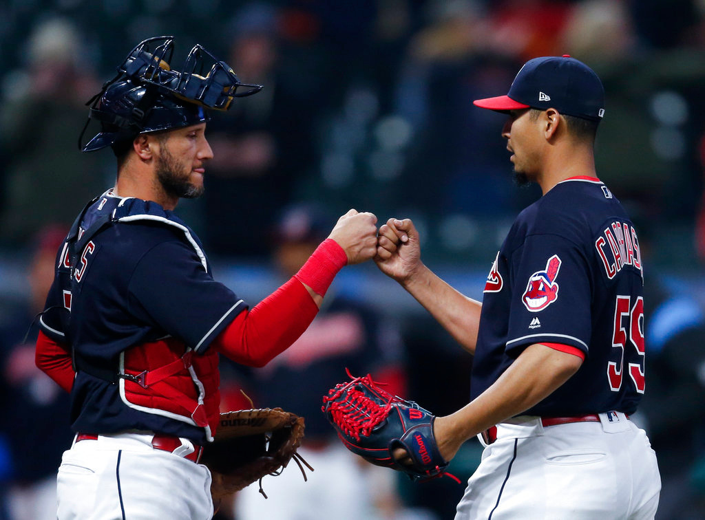. Cleveland Indians starting pitcher Carlos Carrasco (59) celebrates with Yan Gomes (7) after pitching a three-hitter against the Detroit Tigers in a baseball game Wednesday, April 11, 2018, in Cleveland. The Indians won 5-1. (AP Photo/Ron Schwane)