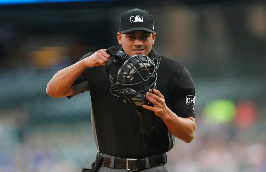 . Home plate umpire Roberto Ortiz adjusts his mask during the first inning of a baseball game between the Detroit Tigers and the Cleveland Indians, Tuesday, May 15, 2018, in Detroit. (AP Photo/Carlos Osorio)