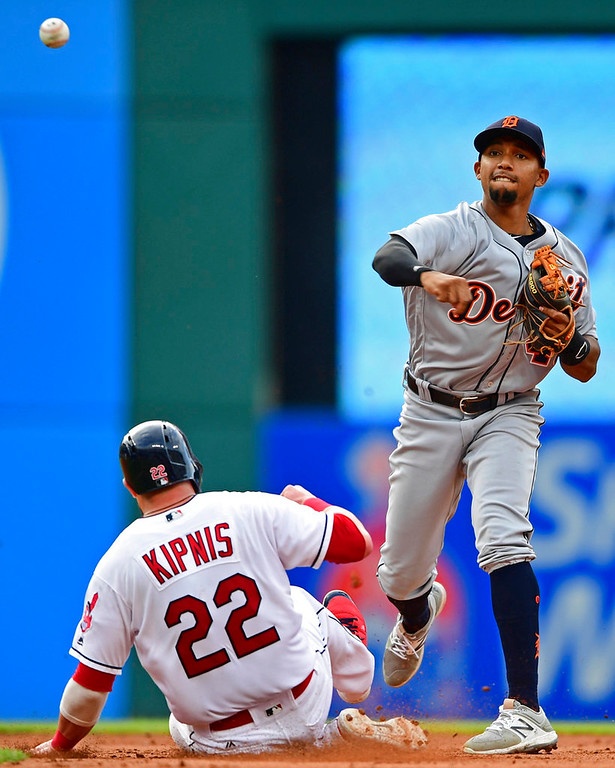 . Detroit Tigers\' Dixon Machado, right, throws to first after getting Cleveland Indians\' Jason Kipnis (22) out at second base in the fourth inning of a baseball game Saturday, June 23, 2018, in Cleveland. Roberto Perez was out at first base. (AP Photo/David Dermer)
